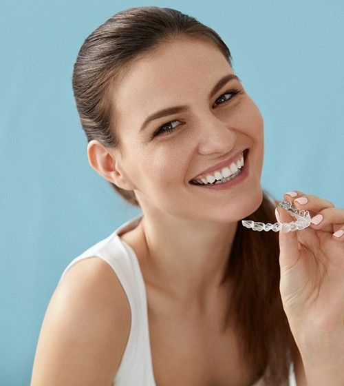 A young woman holding a clear Invisalign aligner and smiling