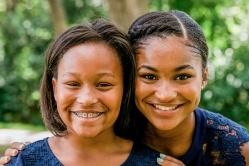 Teen sisters smiling together after orthodontics