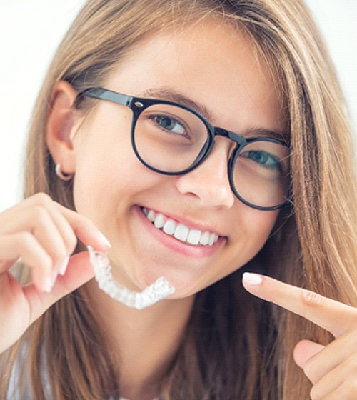 A young girl with glasses pointing to her smile and the aligner she's holding in her hand as part of her Invisalign in Richardson treatment