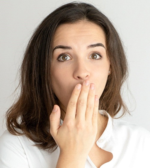 Brunette woman covering mouth, embarrassed by misaligned teeth