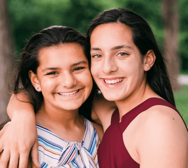 Two teens smiling after receiving dentofacial orthopedics