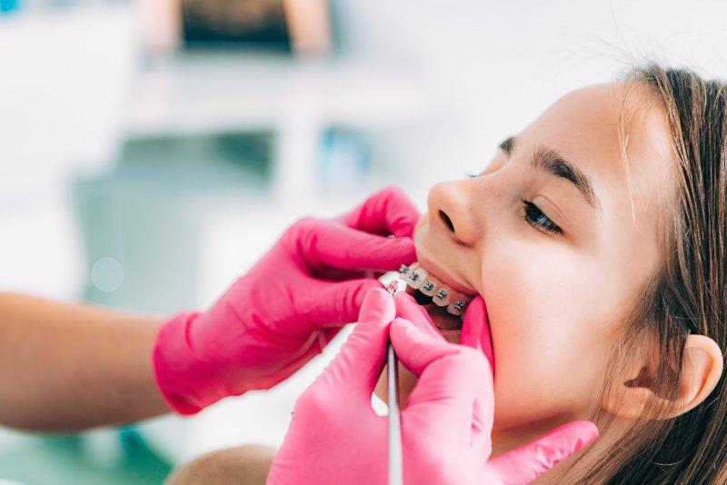 Orthodontist examining patient's braces